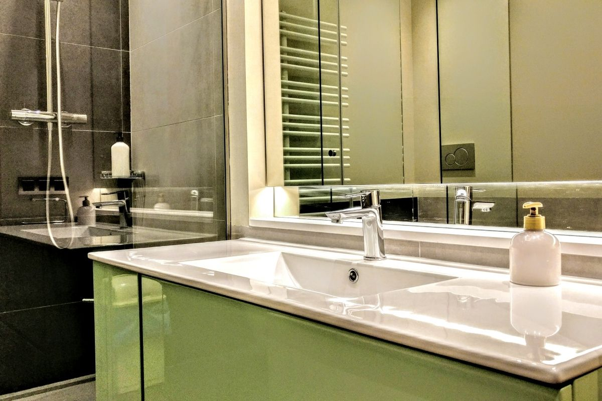 ensuite master bath with a jetted bathtub and a separated shower cabin with rainshower system in this luxury apartment for rent short term in Barcelona