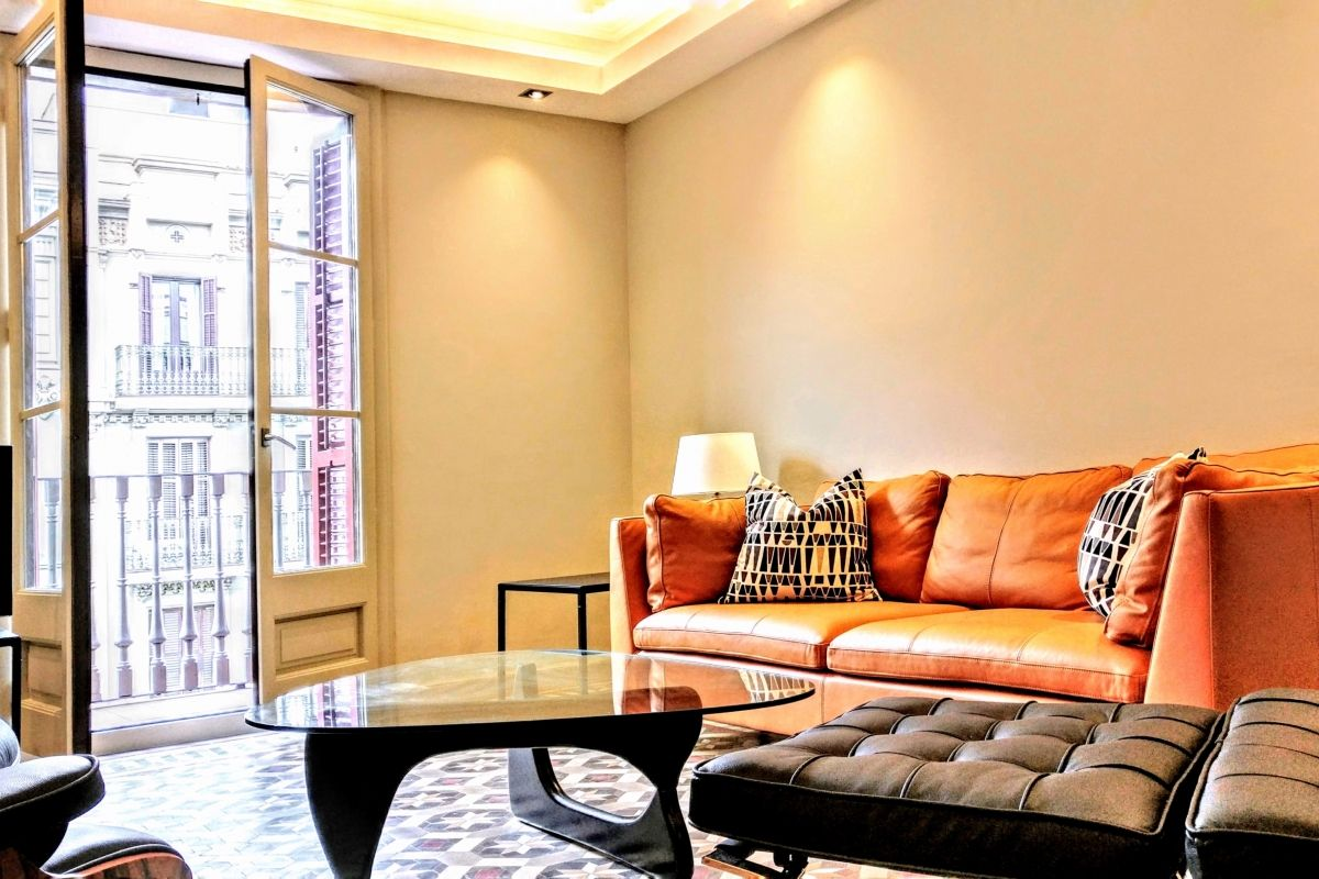 signature leather furniture and sofa at the Dandi luxury apartment for short term rentals in Barcelona. You will relax sitting in the Barcelona chair and ottoman and the Noguchi coffe table that rounds the scene.