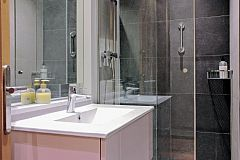 general view of one of the bathrooms with shower cabin and washbasin in the Dandi apartment for rent in Barcelona