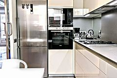 sleek modern kitchen with stainless steel apliances and mirror splashbacks