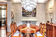 In the dining area, the classy mahogany table and chairs stand out under the massive Artichoke lamp