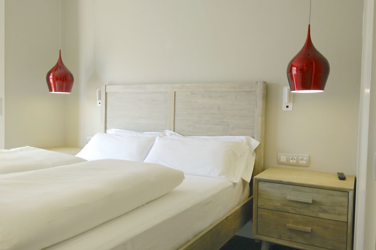 dramatic red hanging lamps next to the headboard in the master bedroom