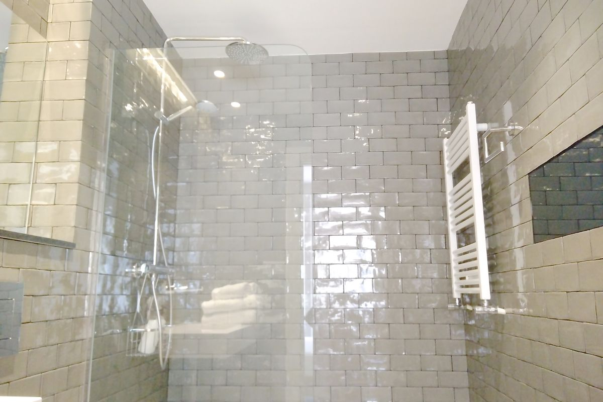 ensuite bathroom with rainfall shower head in this pentouse for rent in Barcelona