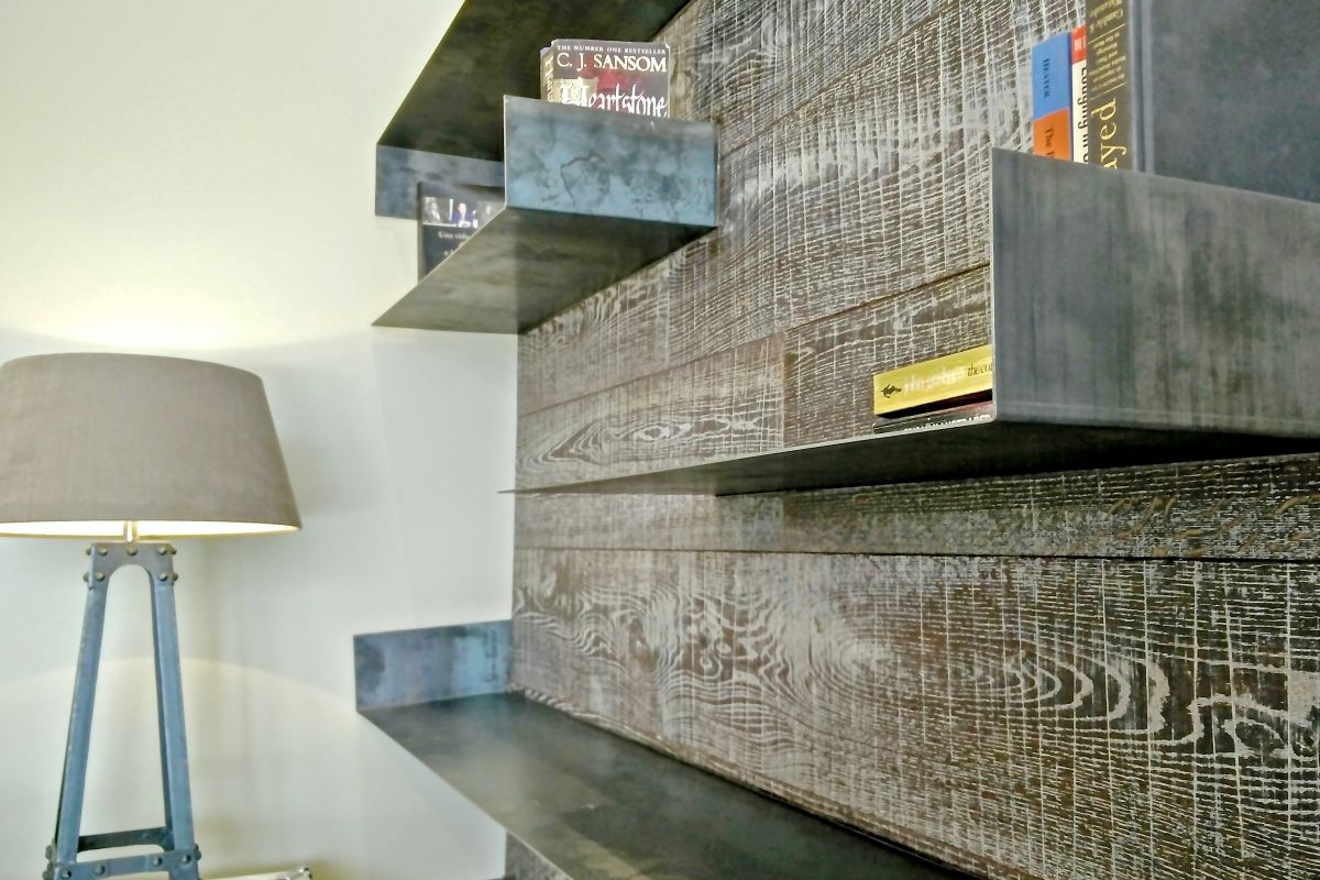 the superb platform flooring crawls up on the wall to create a bookcase to place some interesting books to shere you moments of relax in this Ferran Batik penthouse apartment for rent in Barcelona