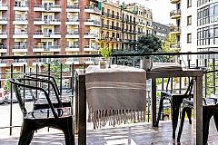 the lovely furnished terrace has a large glass dining table and four metal chairs
