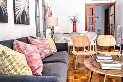 the living area with this comfortable sofa and designer chairs at the Noname apartment is very convenient for family trips to Barcelona during your short term rental stay