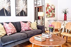 the Noname apartment living area with palm tree leaves paintings and fluffy cushions in the sofa is perfect for vacation getaways in Barcelona Eixample left