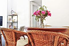 detail of the dining area with a wooden antique table and the rattan armchairs