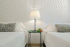 detail of the beautiful and original white headboards and bedside table in the second bedroom