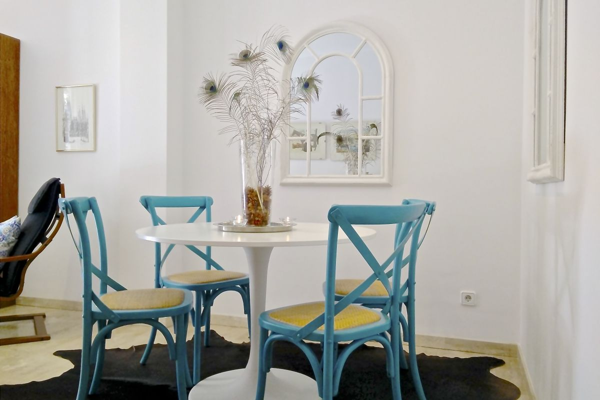 detail of the dining area with the lovely blue chairs and a pair of mirrors