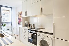 fully equipped pristine white kitchen with washer and dryer