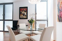 the glass dining table has room enough for all the guests staying in the apartment
