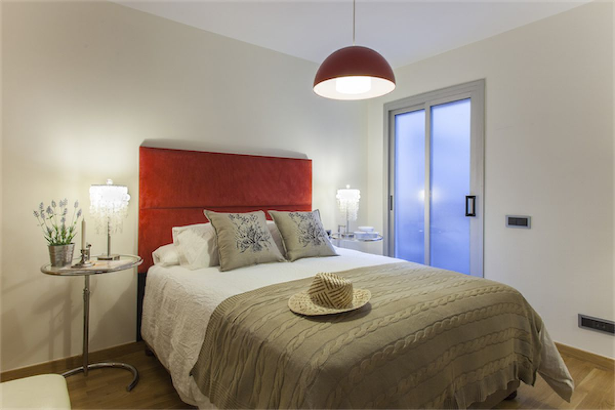 bedroom 2 with a queen bed size 150x200 cm with a large red velvet headboard matching the ceiling lamp
