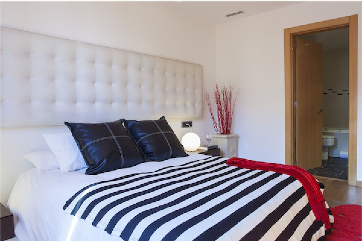 LaMimosa apartment for rent in Barcelona master bedroom with a large headboard covered in tufted white fabric