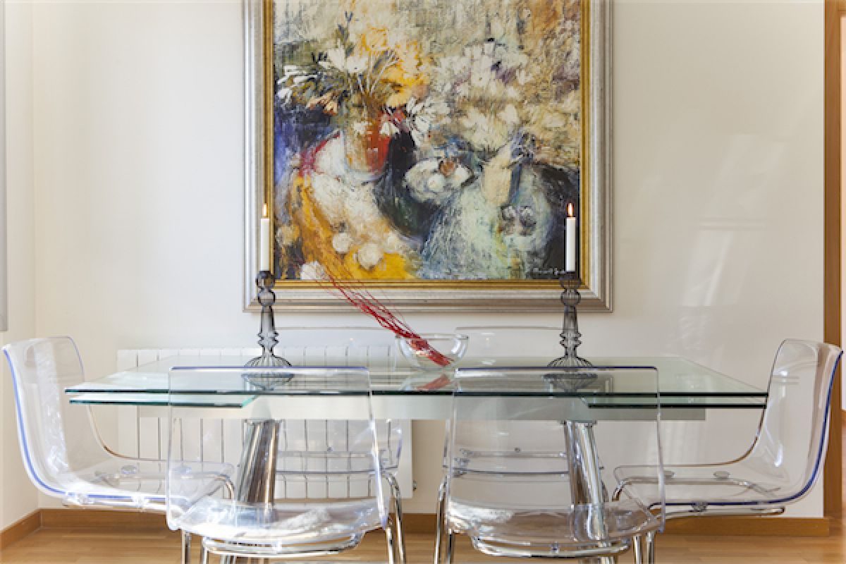 sleek dining area with a glass table, transparent chairs and original oil painting