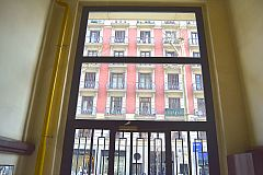 dramatic entrance glass and iron door to the building that houses this LaMimosa luxury apartment for rent in Barcelona Eixample