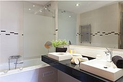 master ensuite bath with jetted bathtub and separate shower cabin in this LaMimosa apartment rental in Barcelona Eixample next to Passeig de Gràcia