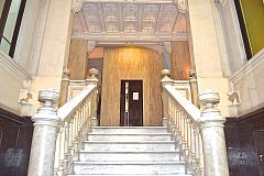 marble staircase to the lift in the main entrance of the building in this LaMimosa apartment for rent in Barcelona center