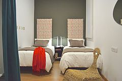 KissMe apartment for rent in Barcelona second bedroom with two dramatic headboards covered in the typical fabric from Mallorca island