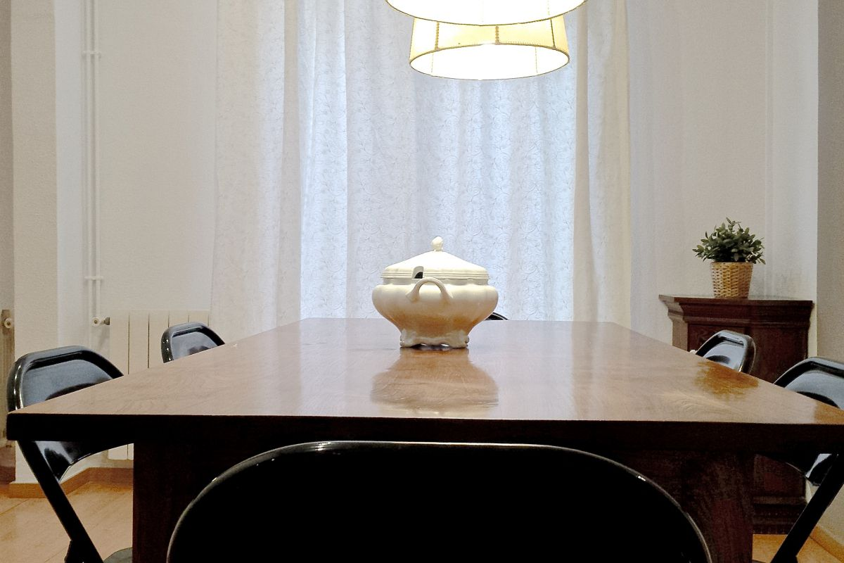 a vintage mahogany table is a luxury for six people at the Macca with balcony luxury apartment for monthly rentals in Barcelona Gothic quarter city center