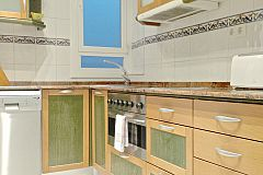 general view of the kitchen in the Macca apartment with balcony in Barcelona with oven and dishwasher