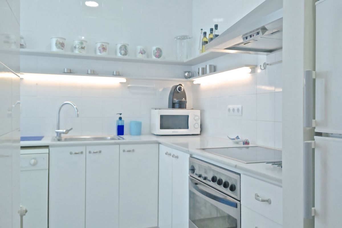 fully equipped white kitchen with washer and dishwasher