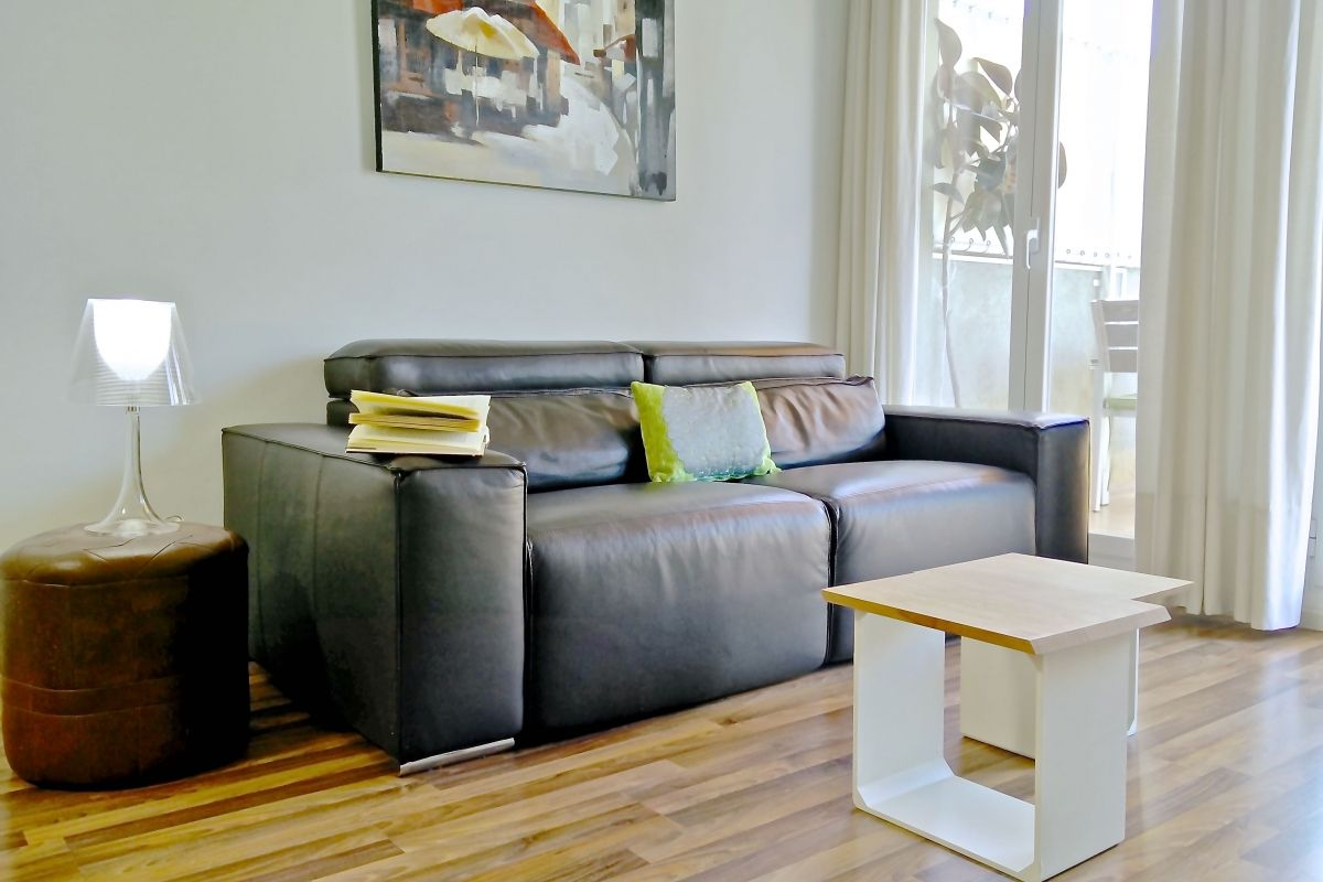 Lounge with a comfortable leather sofa in the Penthouse apartment with terrace for rent in Barcelona Eixample close to Sants train station