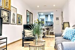a comfortable sofa, two relaxing armchairs and a huge plasma screen TV, create the living areain this monthly rental in Barcelona