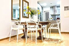 A vintage mahogany table is a luxury for six people, who may gracefully sit on six Curve dining chairs by Kartell at the Parsifal with balcony luxury apartment for short term rentals in Barcelona