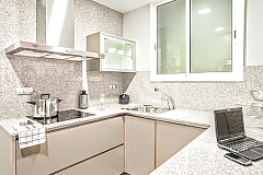 fully equipped grey and white kitchen with washer and dryer