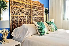 dradramatic wooden headboard fitting to perfection the bed cushions, bed lamps and that tropical vibe filling the ambiencematic fabric headboards fitting to perfection the bed cushions and plaids