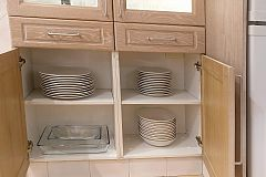 detail of the cabinets in the kitchen with all the chinaware and glassware and cutlery that you may need during your stay