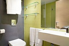 full bathroom with shower cabin, modern sink detail with sleek faucets